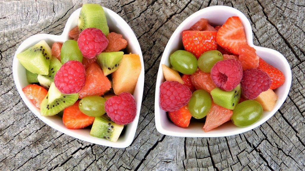deux salades de fruits dans ramequins en forme de coeur avec morceaux de fraise kiwi framboises raisins